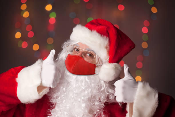 Santa wearing a face covering, with thumbs up.